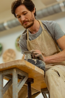 Показывает свои навыки. короткошерстный сосредоточенный парень в фартуке, вырезающий на профессиональном колесе изящные фигурки из мокрой глины