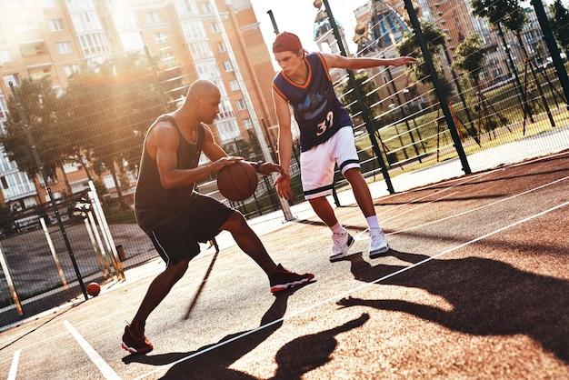 彼のスキルを示しています。屋外で時間を過ごしながらバスケットボールをするスポーツウェアの2人の若い男性
