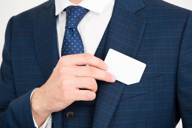 Показывает свою визитную карточку. мужская рука берет карту из кармана костюма. удостоверение личности. экспонат. контактная информация. официальный повод. деловая информация, копия пространства.