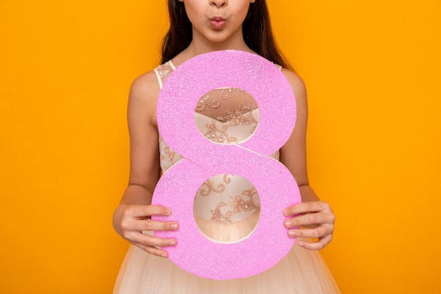 Показывая жест поцелуя красивая маленькая девочка в счастливый женский день, держа номер восемь на оранжевой стене