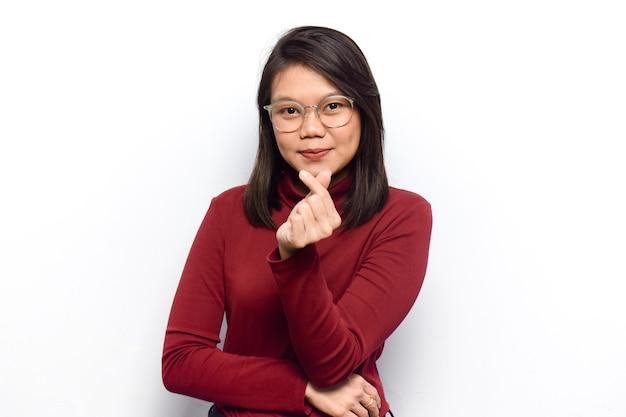 若い美しいアジアの女性の韓国の指の愛を示す白で隔離の赤いシャツを着る