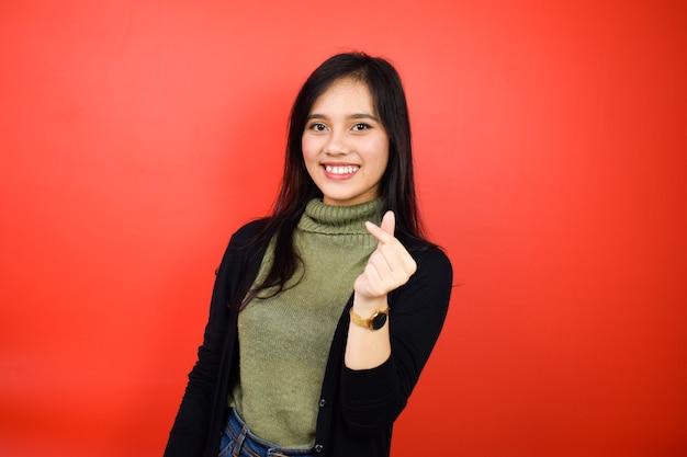赤で隔離の黒いセーターを使用して若い美しいアジアの女性の韓国の愛の指を示しています