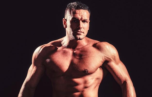 Показаны мускулистый торс. портрет сильного здорового красивого спортивного человека. сильный атлетичный мужчина, показывающий мускулистое тело и пресс с шестью упаковками.