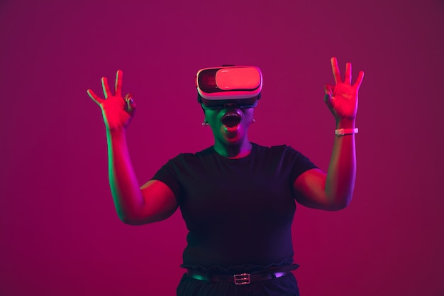 Showing nice sign. african-american young woman's portrait on purple background. beautiful model in vr-headset. concept of emotions, facial expression, sales, ad, inclusion, diversity. copyspace.