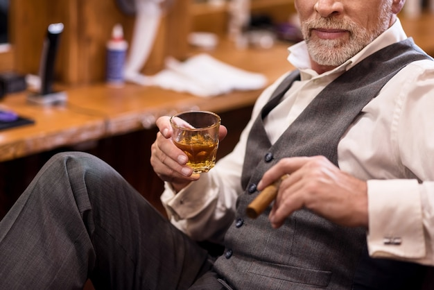 自慢している。ウイスキーグラスと葉巻と肘掛け椅子に座って豪華なスーツを着ている年配のひげを生やした男のクローズアップ。