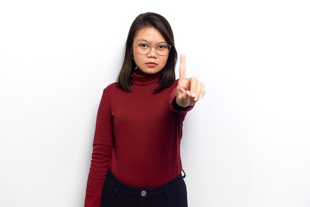 若い美しいアジアの女性の1本の指を示す白い背景で隔離の赤いシャツを着る