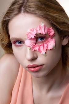 花びらを見せています。ポーズをとっている間、顔に小さなピンクの花びらを示すピンクのアイシェードを持つ青い目のモデル