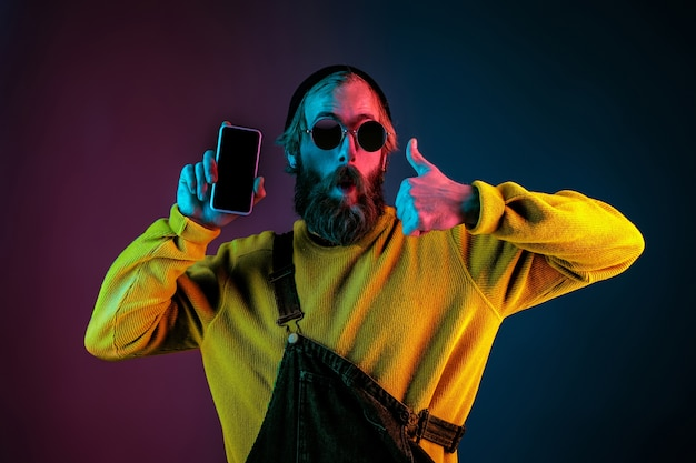 Showing phone's blank screen. caucasian man's portrait on gradient studio background in neon light. beautiful male model with hipster style. concept of human emotions, facial expression, sales, ad.