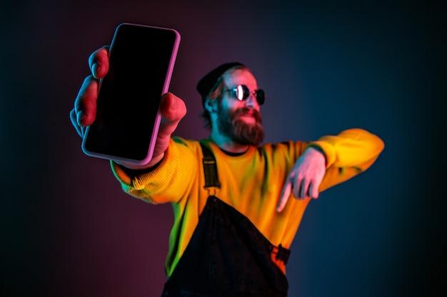電話の空白の画面を表示しています。ネオンの光のグラデーションスタジオの背景に白人男性の肖像画。流行に敏感なスタイルの美しい男性モデル。人間の感情、顔の表情、販売、広告の概念。