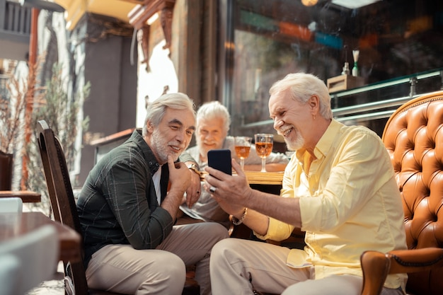 사진을 표시합니다. 그의 오랜 친구에게 사진을 보여주는 노란색 셔츠를 입고 수염 난된 남자