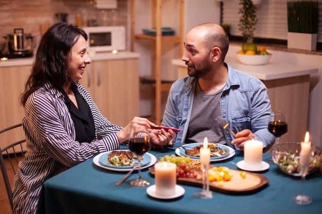 Mostrando test di gravidanza positivo al marito durante una cena romantica. coppia emozionata che sorride, si abbraccia e si bacia per questa grande notizia. incinta, giovane moglie felice per il risultato che abbraccia l'uomo.