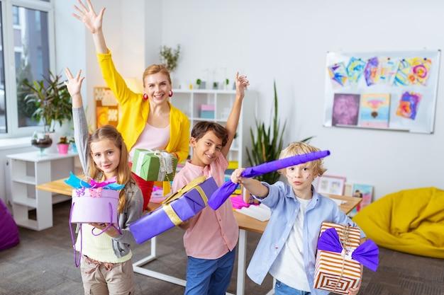 Показывает настоящие коробки. трое учеников и веселый учитель демонстрируют удивительные подарочные коробки после украшения