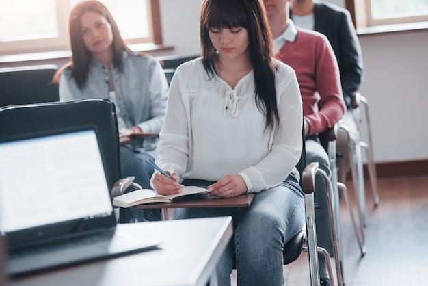 プレゼンテーションを表示しています。昼間の近代的な教室でのビジネス会議での人々のグループ