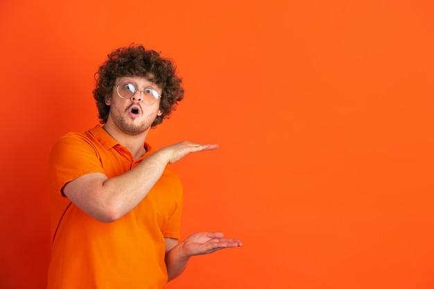 Показывает что-то большое. монохромный портрет кавказского молодого человека на оранжевой стене. красивая мужская фигурная модель в стиле casual. понятие человеческих эмоций, выражения лица, продаж, рекламы.
