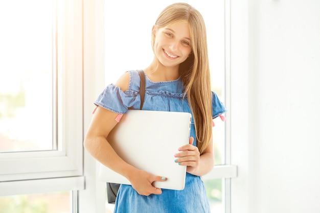 屋内でバックパックとラップトップを持つ立っている女の子を表示
