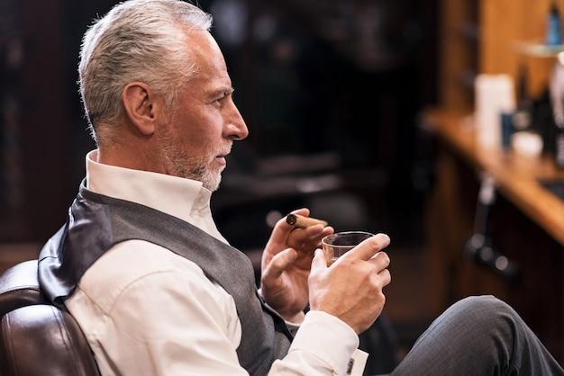 Отображение статуса. вид сбоку красивого старшего человека в роскошном костюме, сидящего на кресле с бокалом коньяка и сигарой.