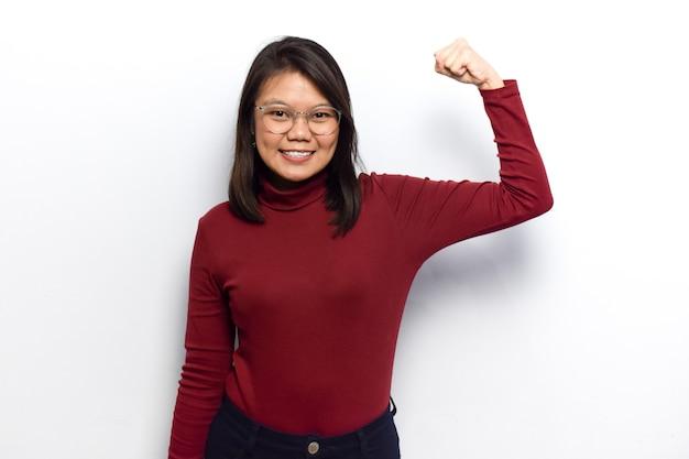 Показывая силу и поднимая руки, молодые красивые азиатские женщины одевают красную рубашку, изолированную на белом