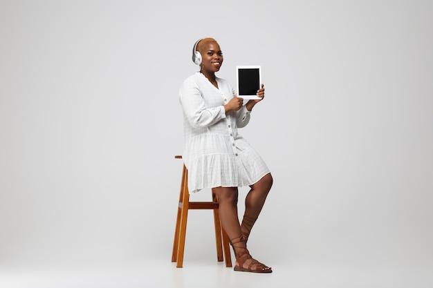 태블릿, 빈 화면을 표시합니다. 회색 배경에 평상복에 헤드폰을 끼고 있는 젊은 여성. bodypositive, 페미니즘, 아름다움 개념. 플러스 사이즈 사업가, 아름다운 소녀. 포용, 다양성.