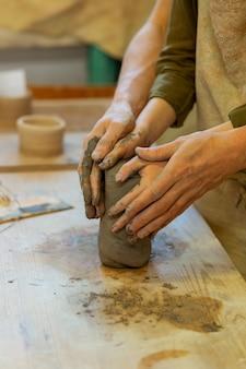 彼らの気持ちを示しています。お互いの手をこすりながら陶芸工房でロマンチックなマスタークラスを持っている熱烈な若いカップル