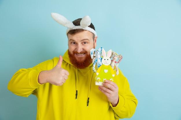 Показывает большой палец вверх. кавказский человек как пасхальный кролик с яркой повседневной одеждой на синем фоне студии. поздравления с пасхой. понятие человеческих эмоций, выражения лица, праздников. copyspace.