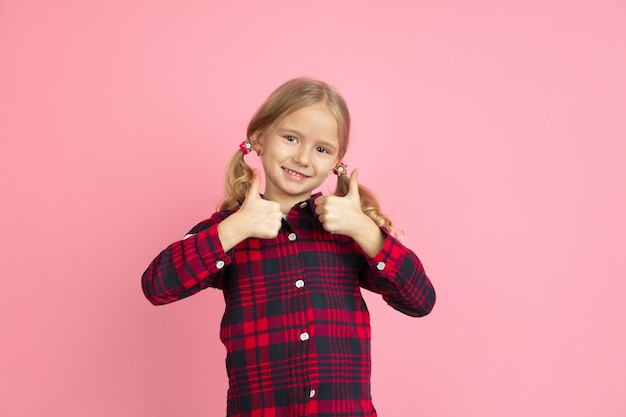 Showing thumbs up. caucasian little girl's portrait on pink wall. beautiful female model with blonde hair. concept of human emotions, facial expression, sales, ad, youth, childhood.