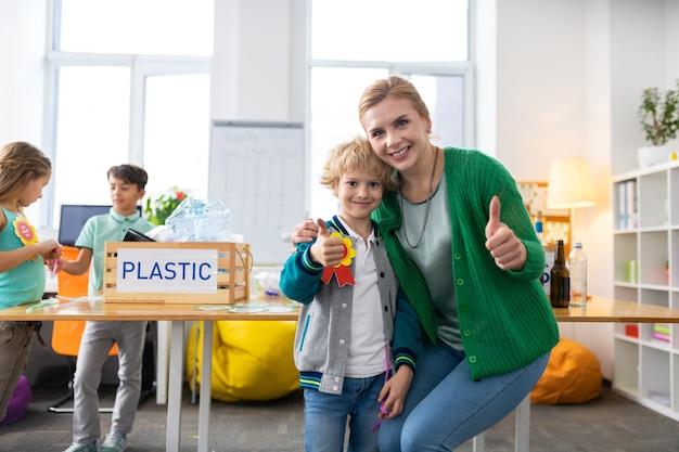 Показывает палец вверх. учитель и школьник показывают палец вверх после успешной экологической кампании в школе