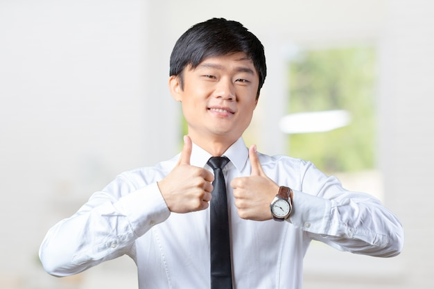 Showing thumbs young asian business man