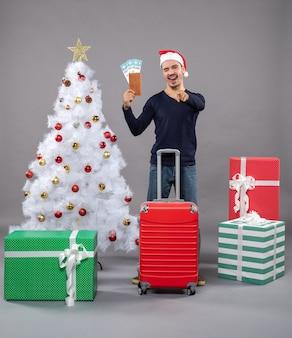 Mostrando la lingua uomo con la valigia rossa che mostra i suoi biglietti di viaggio intorno all'albero di natale bianco e regali su grigio