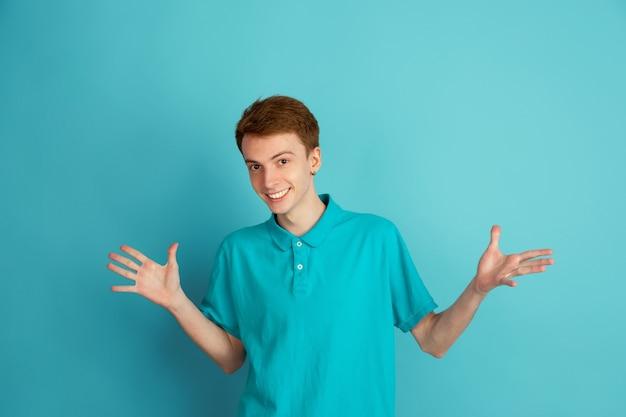 보여주는, 불확실합니다. 파란색 벽, 단색에 고립 된 백인 젊은 남자의 현대 초상화. 아름다운 남성 모델. 인간의 감정, 표정, 판매, 광고, 유행의 개념.