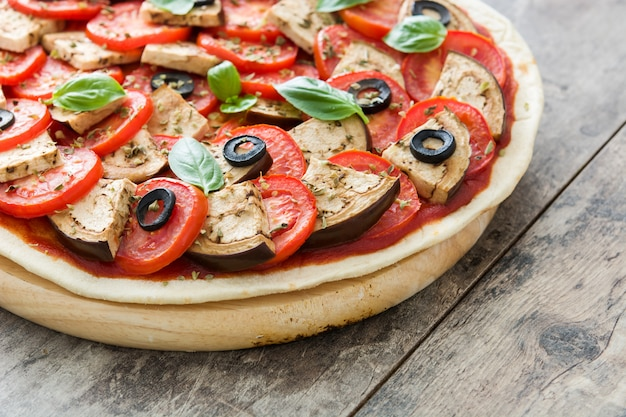 Showing vegetarian pizza with eggplant, tomato, black olives, oregano and basil on wooden table