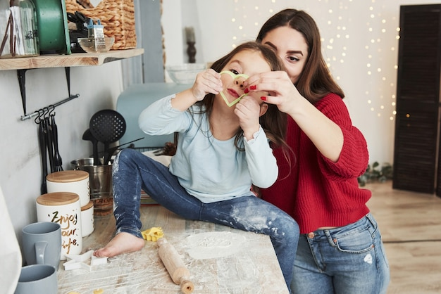 쿠키에 대한 심장 모양의 녹색 형태를 보여줍니다. 가족 초상화. 엄마와 딸이 부엌에서 즐거운 시간을 보냅니다.
