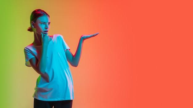 表示中。ネオンの光のグラデーション緑オレンジスタジオの背景に若い白人の女の子の肖像画。若者の概念、人間の感情、表情、販売、広告。美しい十代のモデル。チラシ