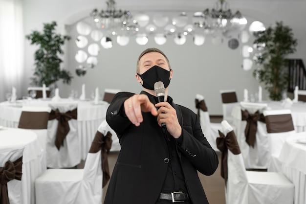 Шоумен в костюме и защитной маске с микрофоном в руках в банкетном зале расторана.