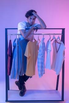 쇼룸. 옷을 옷걸이 근처에 서 사려 깊은 찾고 아프리카 계 미국인 젊은 남자