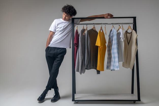 쇼룸. 옷을 옷걸이 근처에 서있는 곱슬 머리 젊은 남자