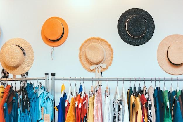 壁には婦人服と夏の麦わら帽子のショールーム店がぶら下がっています。カラフルな衣装のラックハンガー。モダンなミニマルなインテリア