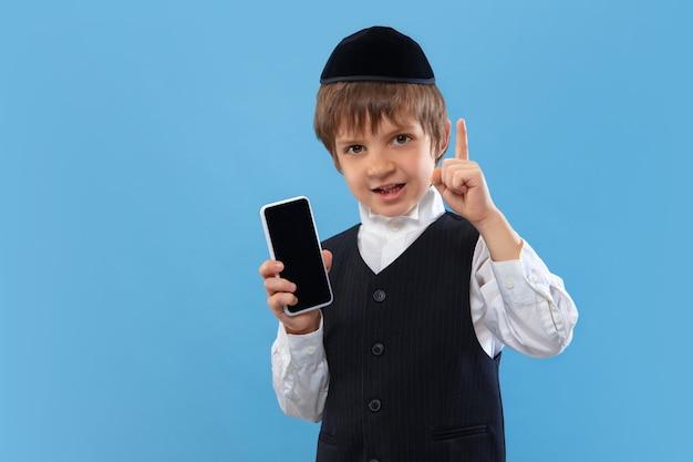 空白の電話画面を表示します。青い壁に分離された正統派ユダヤ人の少年の肖像画。プリム、ビジネス、お祭り、休日、子供時代、お祝いのペサッハまたは過越の祭り、ユダヤ教、宗教の概念。