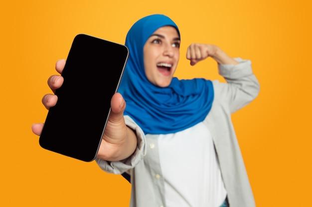 空白の電話画面を表示黄色の壁に隔離された若いイスラム教徒の女性