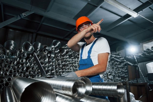 Показывает пункт назначения указательным пальцем. мужчина в военной форме работает на производстве. современные промышленные технологии.