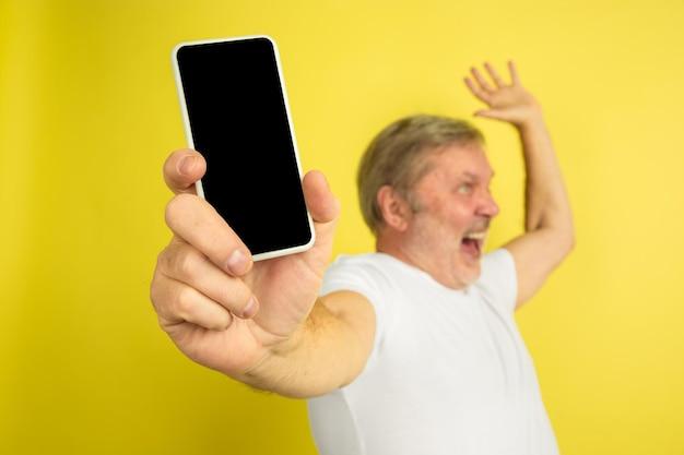 위쪽을 가리키는 휴대폰의 빈 화면을 표시합니다. 노란색 스튜디오 배경에 백인 남자 초상화입니다. 흰 셔츠에 아름 다운 남성 모델입니다.