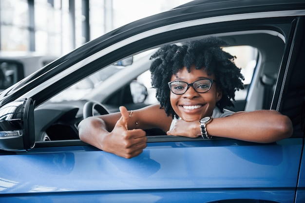 Shows thumb up. young african american woman sits inside of new modern car.