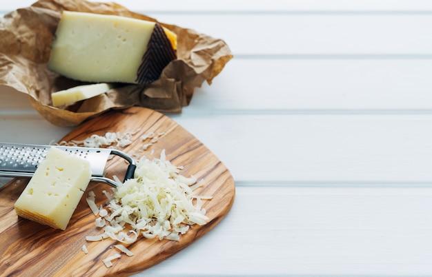 チーズおろし器とチーズのかけらをキッチンボードに載せた細切りチーズ。キッチンのコンセプト。
