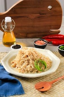 Нарезанная курица на кремовой тарелке, приправленная различными травами. в индонезии обычно используется для фарша lemper ayam.