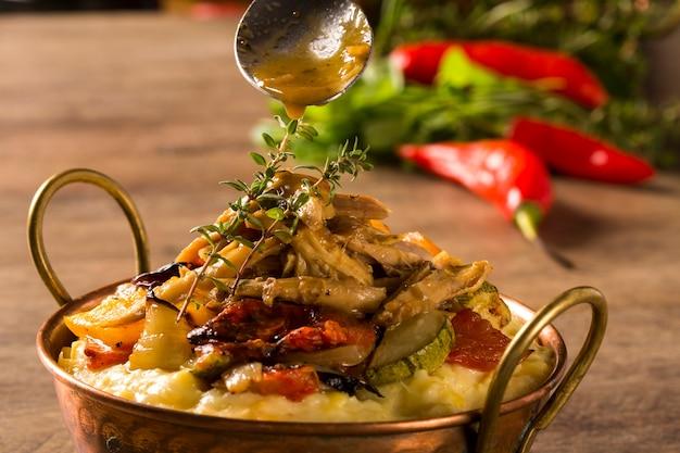 マッシュポテトと野菜をテーブルに盛り付けた細切りチキン