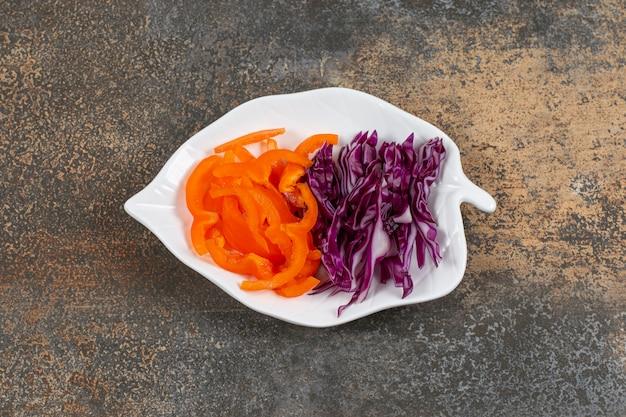 Измельченная фиолетовая капуста и перец на белой тарелке.