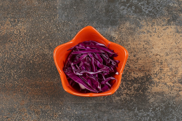 Измельченная фиолетовая капуста в оранжевой миске.
