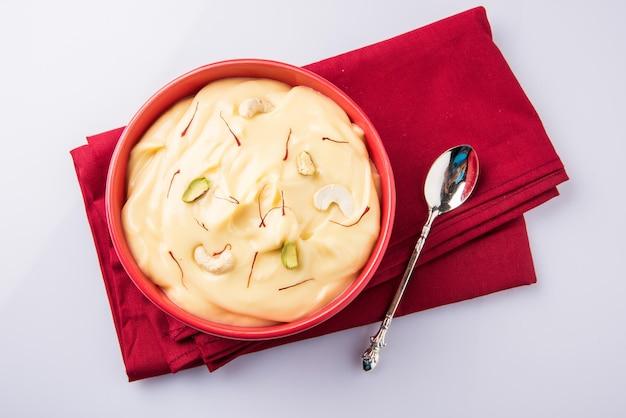 Shrikhand는 말린 과일과 사프란으로 장식된 스트레인 요구르트로 만든 인도의 달콤한 요리입니다. 세라믹 그릇에 제공됩니다. 화려하거나 나무 배경 위에 격리. 선택적 초점