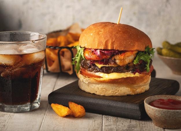 エビとビーフのハンバーガー、飲み物のグラス、フライドポテトのウェッジ、ソース。クローズアップ、明るい背景。