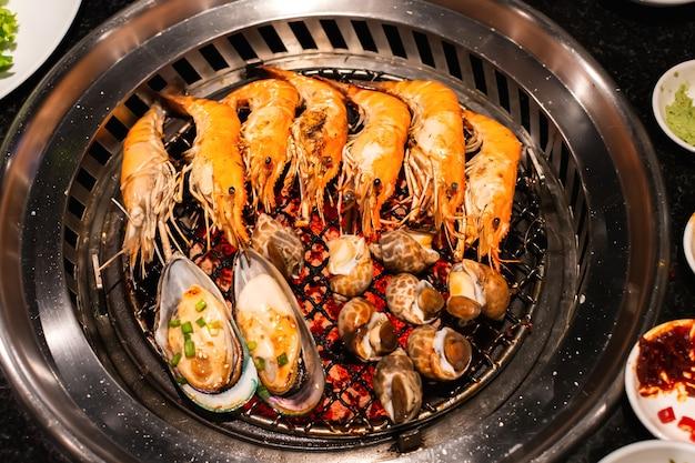 숯불 그릴에 새우와 홍합 껍질 해산물입니다.