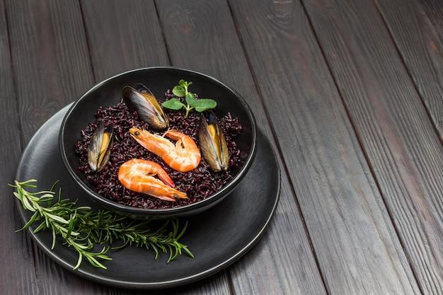 Креветки и мидии с черным рисом в миске. вид сверху. темный деревянный стол.